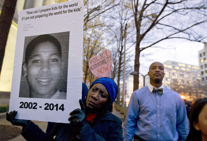 In a 2014 photo, Tomiko Shine holds up a picture of Tamir Rice during a protest in Washington, D.C.