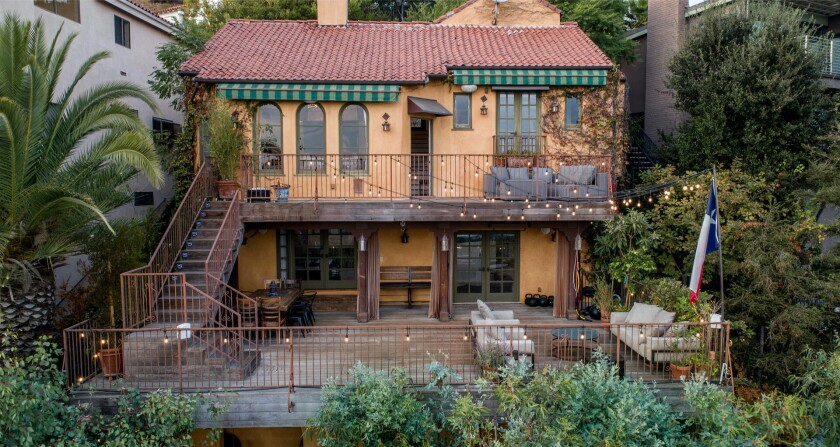 Built in 1925, the hillside home includes two decks, a loggia and a tropical backyard with a bridge, koi pond and fire pit.