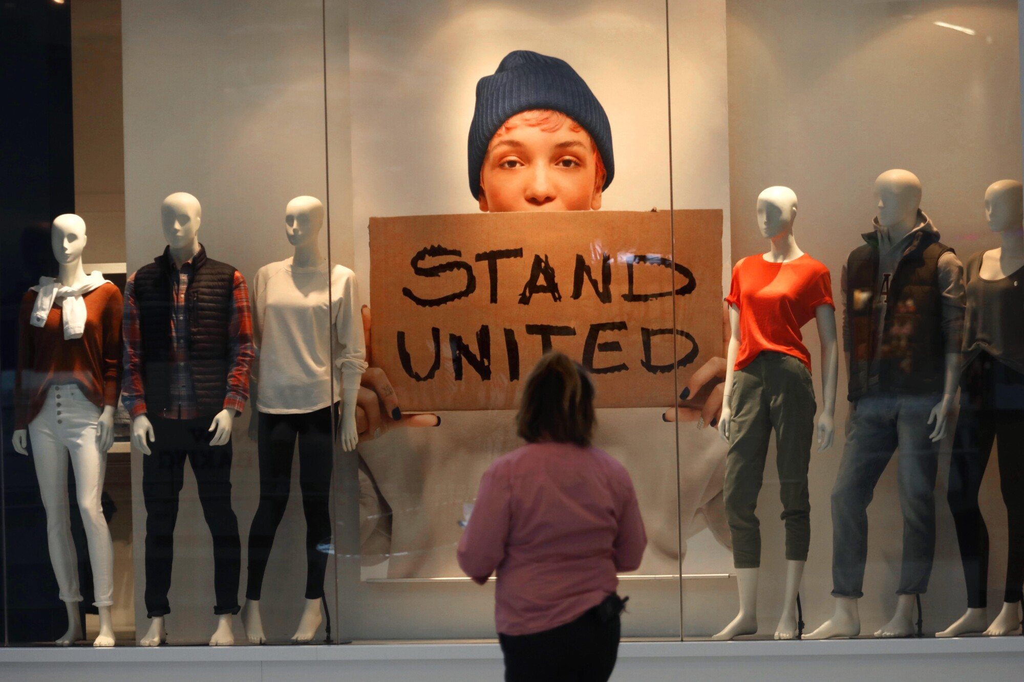 """A woman looks at a window display including a sign saying """"Stand United."""""""