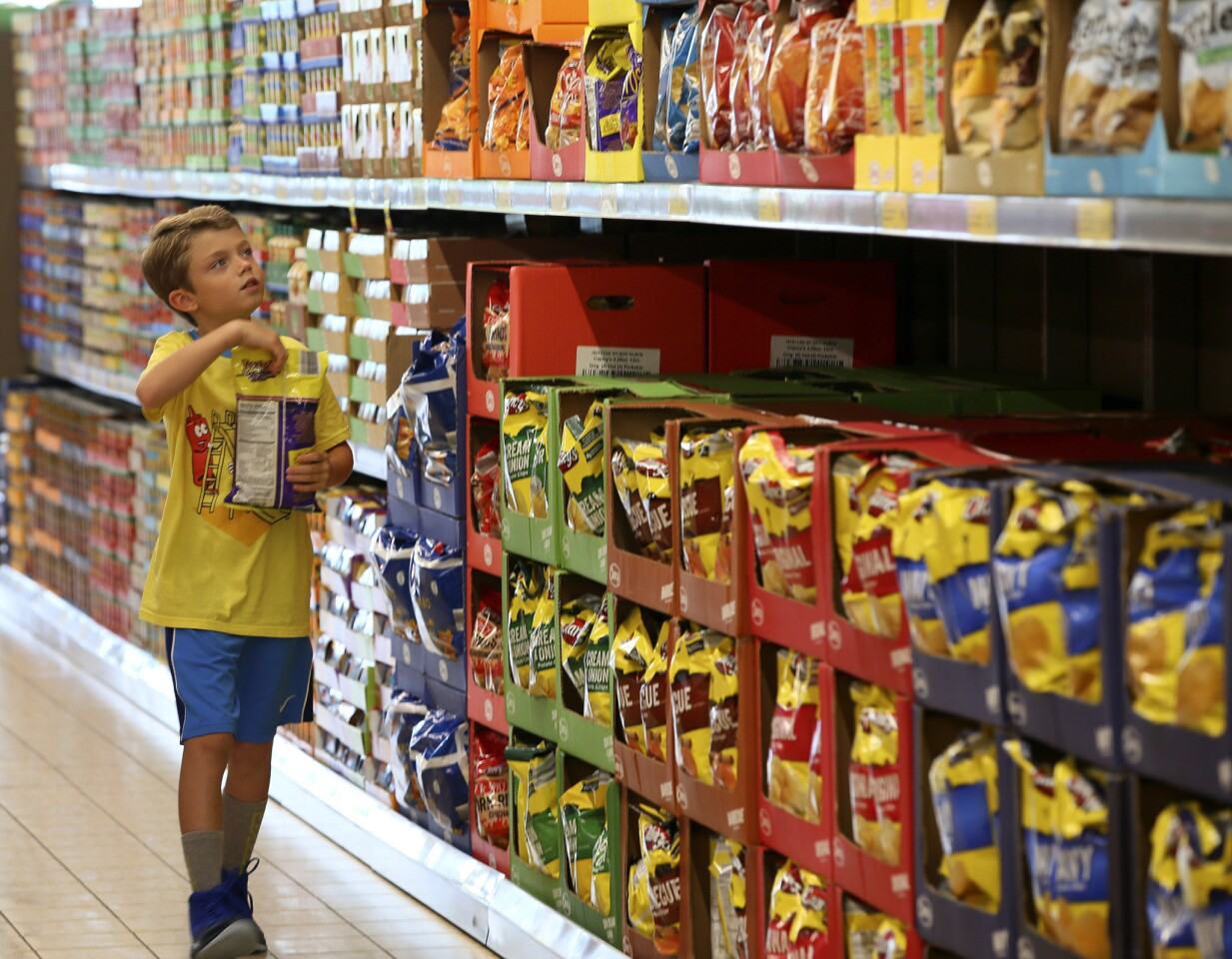 Ethan Bauer, 9, of Geneva, picks out chips at the Aldi Store in St. Charles on August 8, 2018.