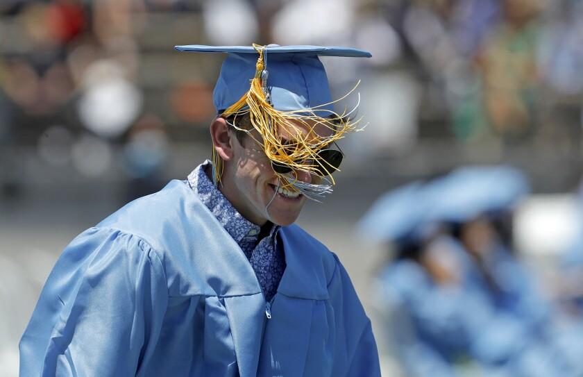 A Corona del Mar graduate has his tassel tangled in the wind.