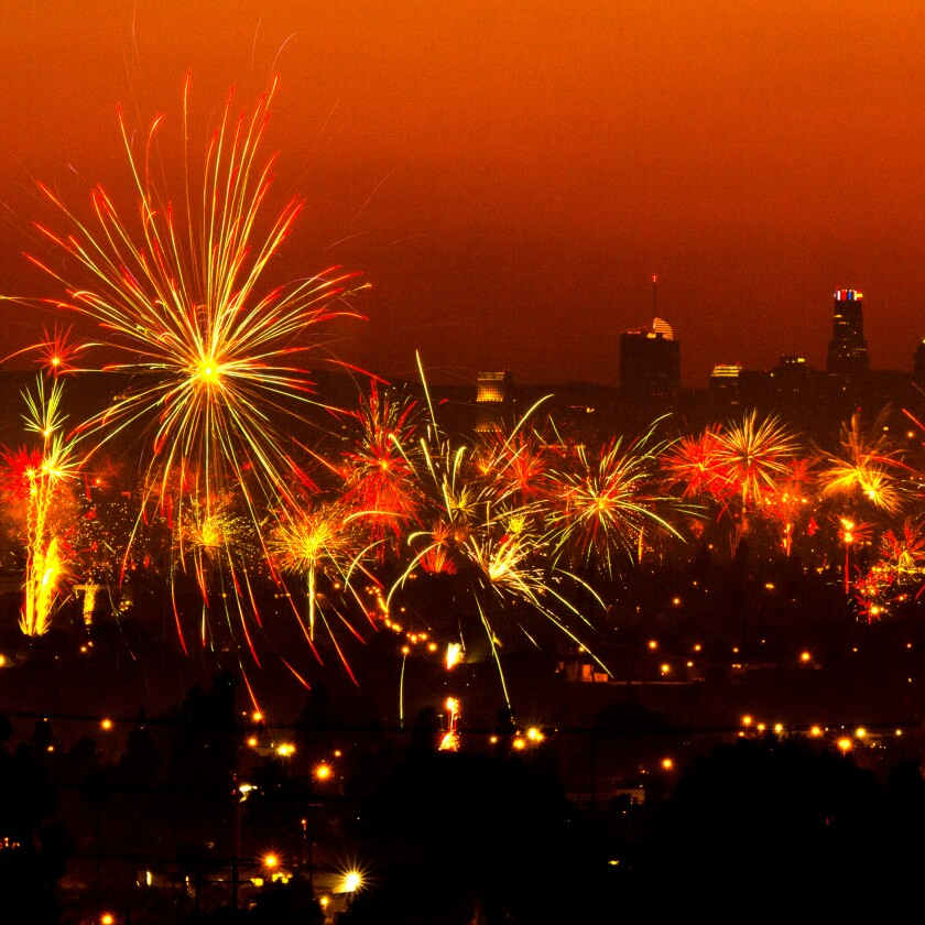 A dark Los Angeles skyline can be seen behind the exploding fireworks.