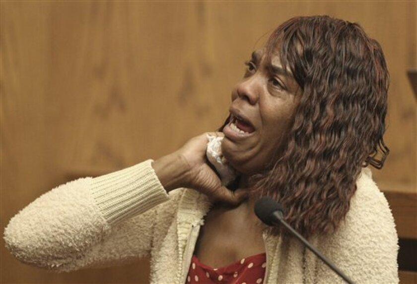 Gladys Wade demonstrates how she was chocked by Anthony Sowell as she testifies during the Sowell trial Thursday, June 30, 2011 in Cleveland. Sowell is charged with killing 11 women and hiding their bodies around his property. Prosecutors say Sowell lured women from his inner-city Cleveland neighbo