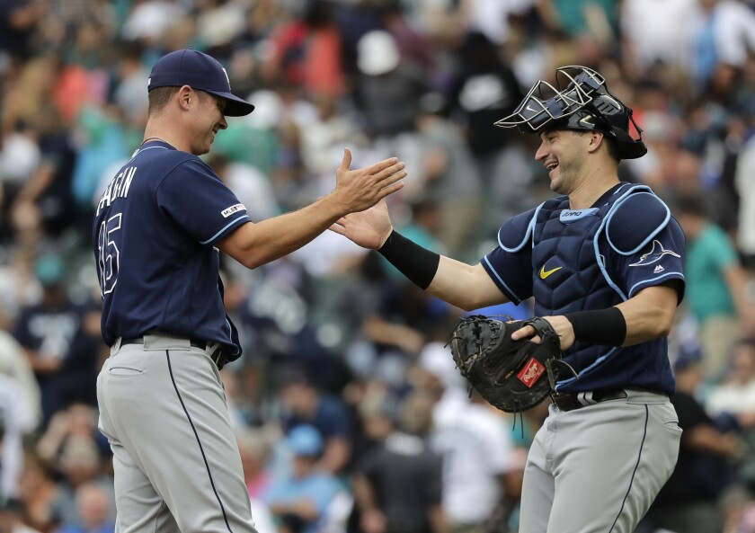Tampa Bay Rays catcher Mike Zunino, right, greets pitcher Emilio Pagan, left, after Pagan earned the save against the Seattle Mariners in an August game.