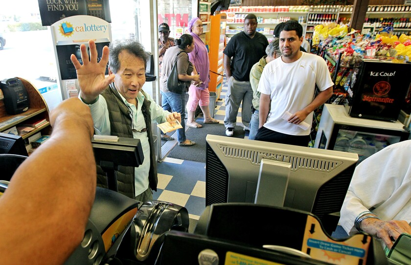 Customer Genaro Ayam-Lau, of Hawthorne, left, waves goodbye to workers at Bluebird Liquor in Hawthorne after purchasing lottery tickets on Monday