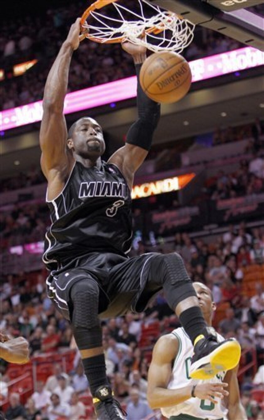 Miami Heat guard Dwyane Wade (3) dunks the ball as Boston Celtics guard Avery Bradley, rear, looks on during the first half of an NBA basketball game, Tuesday, April 10, 2012 in Miami. (AP Photo/Wilfredo Lee)