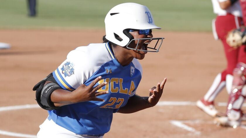 UCLA's Aaliyah Jordan gestures to her team as she runs in after hitting a home run against Oklahoma