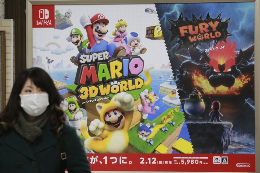 A woman walks by posters of Nintendo in Tokyo, Monday