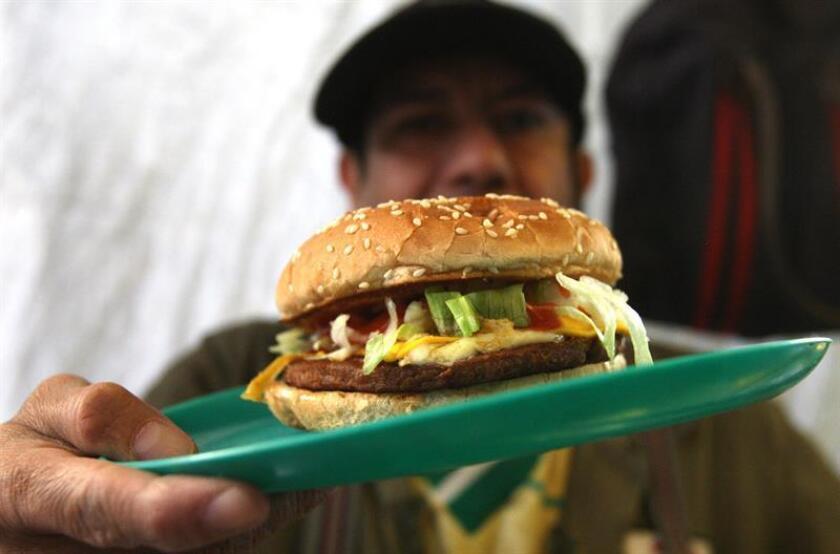 Vista de una persona con una hamburguesa en Ciudad de México. EFE/Archivo