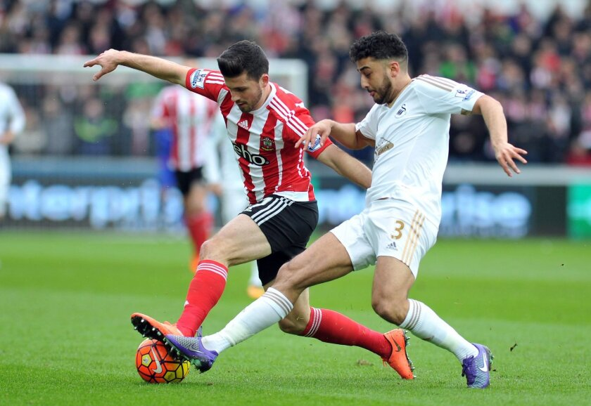Swansea City's Neil Taylor, right, and Southampton's Shane Long battle for the ball during the English Premier League soccer match at the Liberty Stadium, Swansea, Wales, Saturday Feb. 13, 2016. (Simon Galloway/PA via AP) UNITED KINGDOM OUT