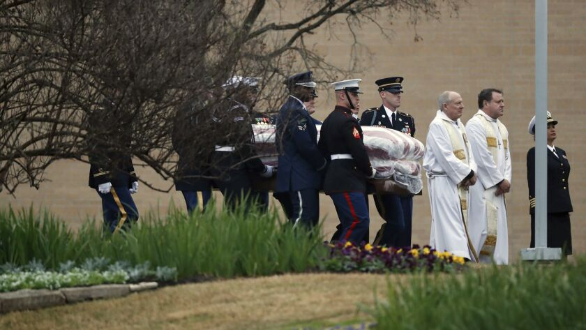 The flag-draped casket of former President George H.W. Bush is carried by a joint services military