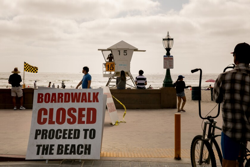 Beachgoers walk along the boardwalk in Mission Beach ahead of Memorial Day Weekend on May 22, 2020 in San Diego, California. The boardwalk is currently supposed to be closed to pedestrians except to cross to and from the sand.