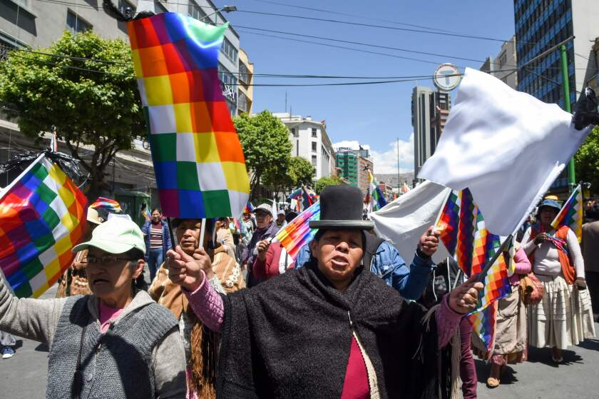 Supporters of Bolivian ex-President Evo Morales demonstrate holding Wiphala flags -representing native peoples- in La Paz. Bolivia's interim president said Sunday she will call new elections soon, as the country struggles with violent unrest a week after the resignation of Evo Morales.