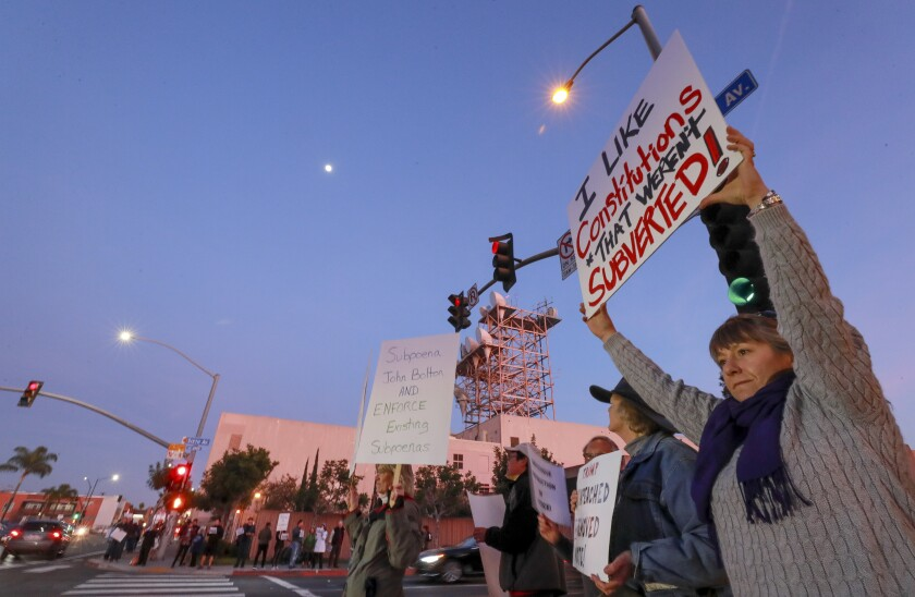 Heather Fay, right, holds a sign as she and around 50 other people gather at the intersection of 6th Avenue and University Avenue in Hillcrest to protest the U.S. Senate's final impeachment trial vote to acquit President Trump on Wednesday, February 5, 2020 in San Diego, California.