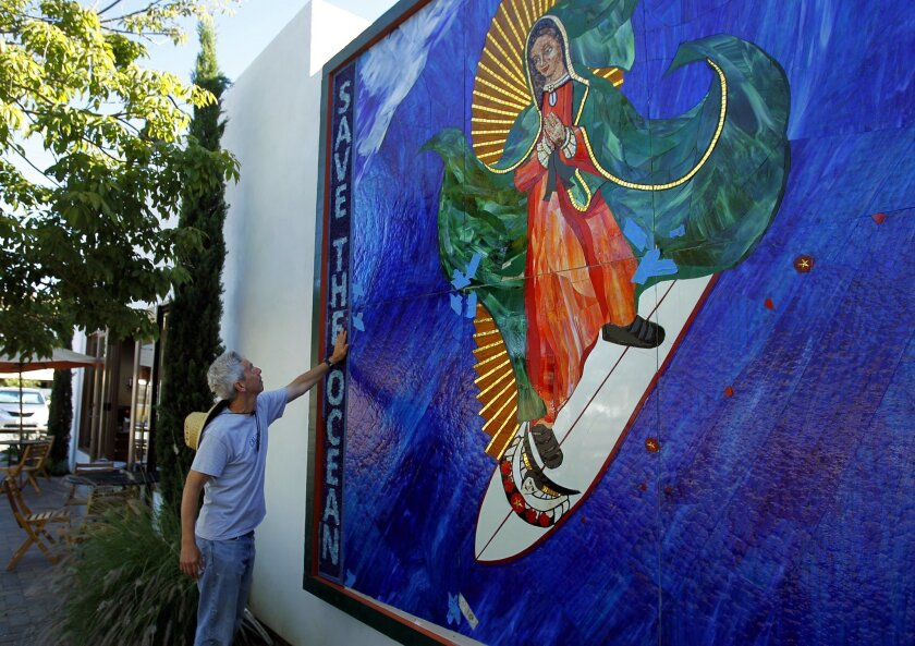 The Surfing Madonna mosaic is at the center of a dispute between Encinitas officials and the charity that owns the artwork.