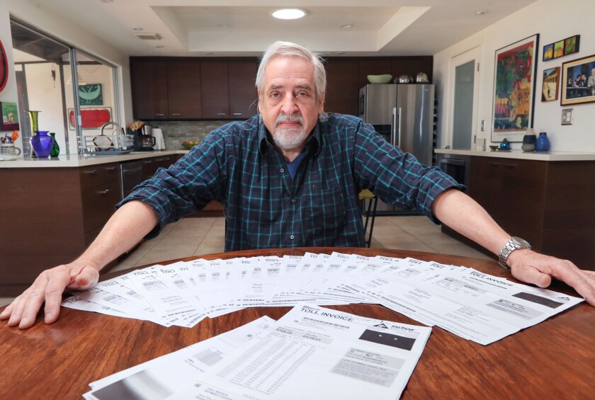 Jim Okerblom with the bridge-toll invoices he received.