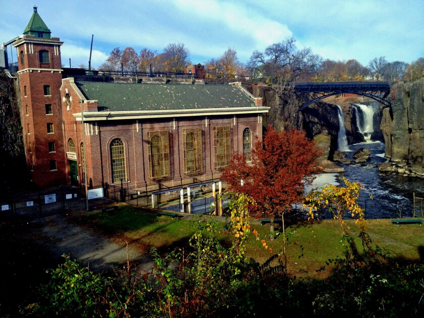 The Great Falls of Paterson, N.J., cascade beyond the SUM powerhouse, built in 1914 when hydroelectric power supplanted the extensive system of raceways and waterwheels that Alexander Hamilton helped envision to make Paterson - and America - great. PATERSON, NJ-- The Great Falls, with the 1914 S.U.M powerhouse in the foreground.