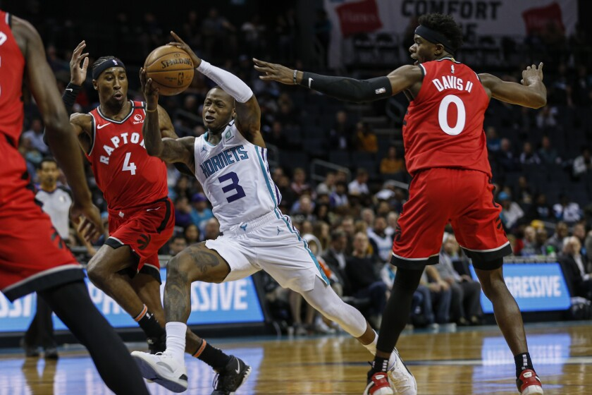 Charlotte Hornets guard Terry Rozier, center, drives between Toronto Raptors forward Rondae Hollis-Jefferson (4) and guard Terence Davis (0)during the first half of an NBA basketball game in Charlotte, N.C., Wednesday, Jan. 8, 2020. (AP Photo/Nell Redmond)