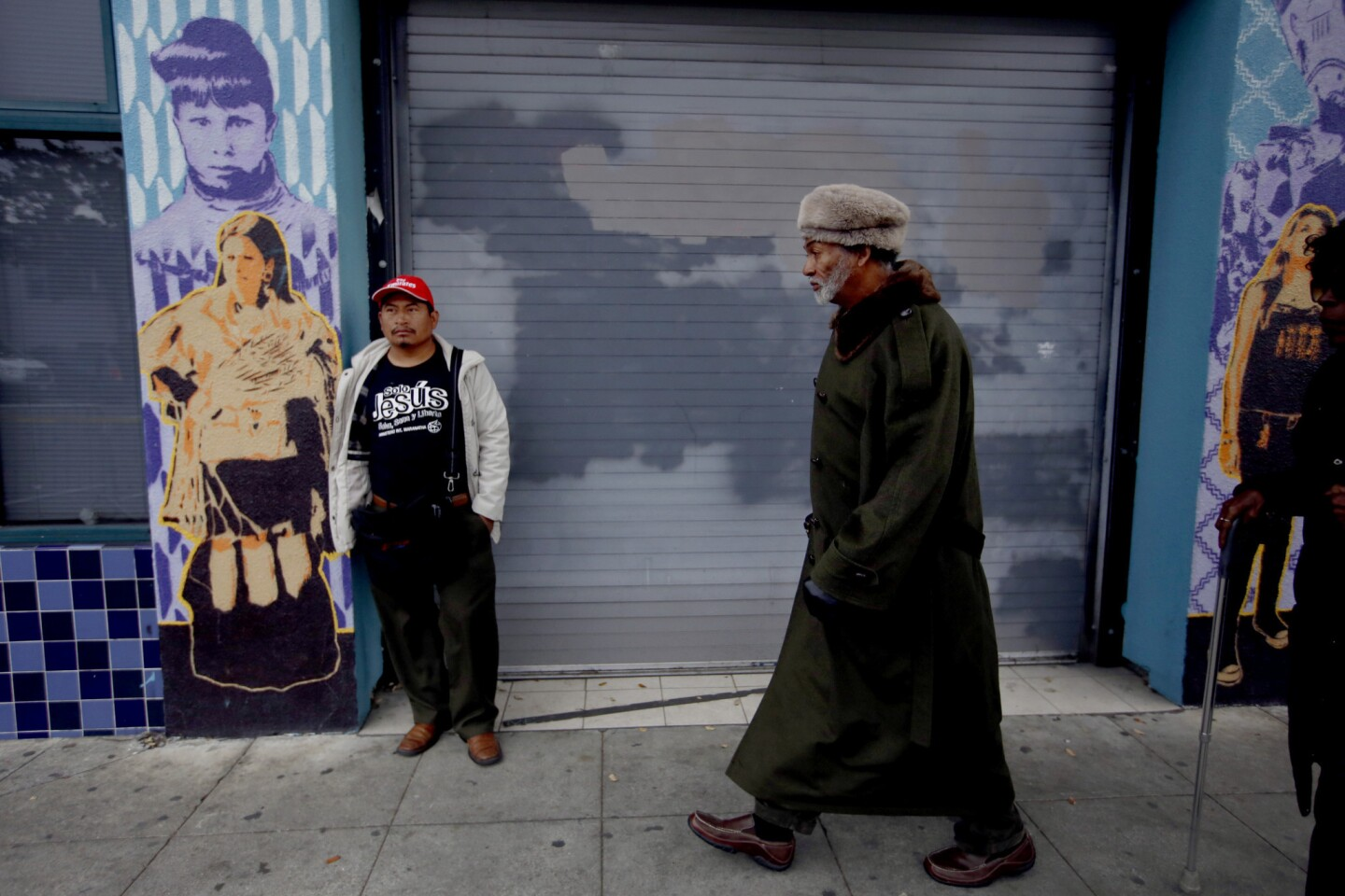 Elias Nolasco, left, 39, of Oakland stands near the site of the warehouse fire as poet Alfred Hayes, right, 69, of Oakland, walks to his dentist appointment in Oakland on Wedneday. Residents described Fruitvale, situated in the flats south of downtown between two freeways, as a largely Latino district of working-class families and small shops.