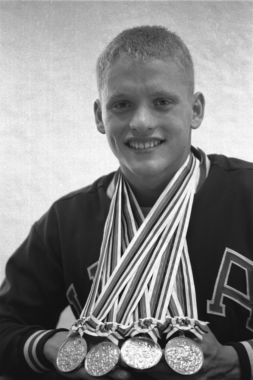 FILE - In this Oct. 18, 1964, file photo, Don Schollander of Lake Oswego, Ore., poses with the four gold medals he won during Olympic swimming competitions in Tokyo. Schollander won the gold medals for the 100 and 400 meters freestyle, and swam legs of the winning 400-meter medley and 800-meter freestyle relays. (AP Photo/File)