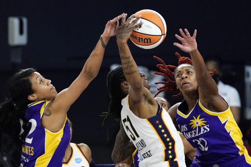 Indiana Fever forward Jessica Breland reaches for a rebound along with Sparks guard Arella Guirantes and guard Bria Holmes.