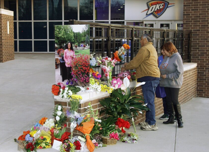 Thunder fans drop off flowers at a memorial for Ingrid Williams, the wife of Thunder assistant coach Monty Williams, who died Wednesday as the result of a car accident Tuesday, before an NBA basketball game between the New Orleans Pelicans and the Oklahoma City Thunder in Oklahoma City, Thursday, F
