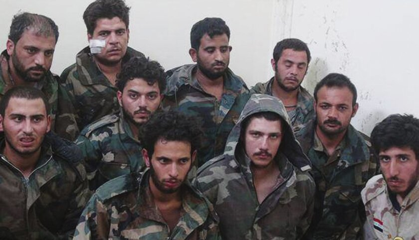This picture released on Sunday, May 24, 2015, by a militant website which had been verified and is consistent with other AP reporting shows Syrian government soldiers who were captured by Islamic state militants in Palmyra area in Syria. The Syrian army is deploying troops in areas near the ancient town of Palmyra in apparent preparation for a counterattack to retake it from the Islamic State group, an official said. (Militant website via AP)