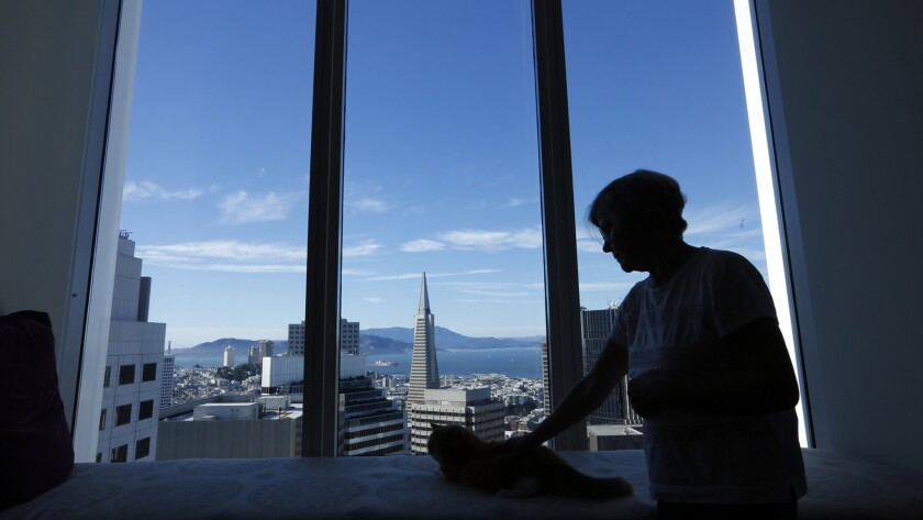Pamela Buttery pets her cat Maximus inside her apartment in the Millennium Tower.