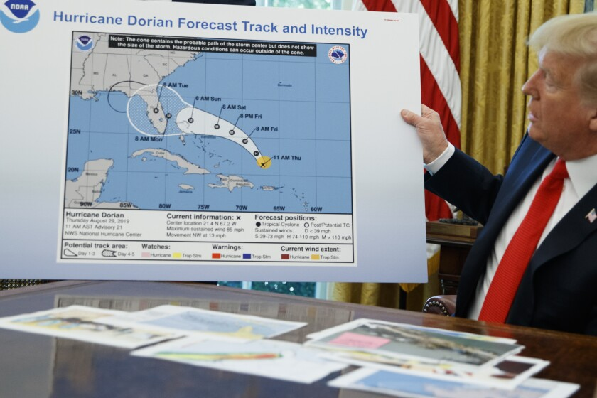 FILE - In this Sept. 4, 2019, file photo, President Donald Trump holds a chart as he talks with reporters after receiving a briefing on Hurricane Dorian in the Oval Office of the White House in Washington. A government watchdog says the Commerce Department is trying to block the findings of an investigation into the agency's role in rebuking forecasters who contradicted President Donald Trump's inaccurate claims about the path of Hurricane Dorian in 2019. (AP Photo/Evan Vucci. File)