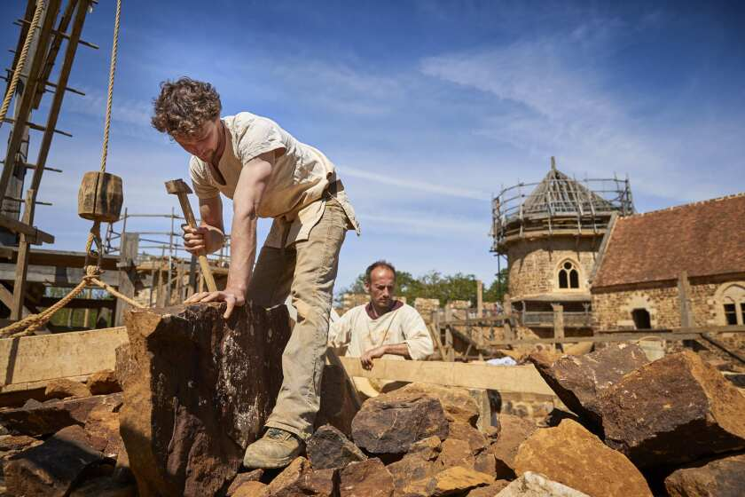 GUEDELON CASTLE, FRANCE - MAY 23: Masons work on building two gothic arches at Guedelon medieval cas