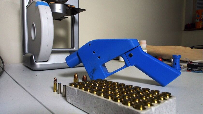 A Liberator pistol next to the 3-D printer on which its components were made, along with a box of ammunition.