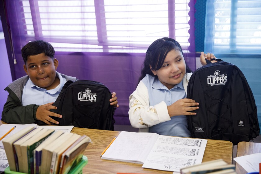 Students hold backpacks from Clippers' Kawhi Leonard after he gave backpacks away to students at One Hundred Seventh Street Elementary School on Tuesday in the Watts neighborhood of Los Angeles.