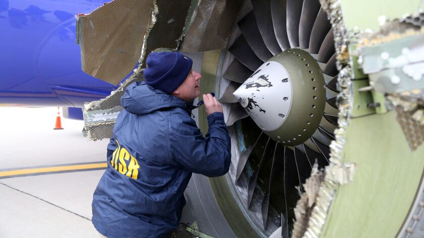A National Transportation Safety Board investigator examines damage to the CFM engine belonging to Southwest Airlines Flight 1380.