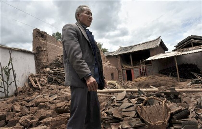 A farmer looks at the debris of his earthen house after an earthquake in Yao'an in southwest China's Yunnan province Saturday July 11, 2009. Thousands camped in tents in southwestern China on Saturday after a magnitude-6.0 earthquake destroyed thousands of homes, killed one person and injured 320. (AP Photo)