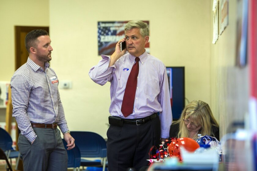 Deputy campaign manger Matthew Rice, left, looks on as San Diego County Supervisor Dave Roberts and volunteer Mary Gaines makes last minute phone calls to get voters out to vote from his Escondido campaign headquarters on Tuesday evening.