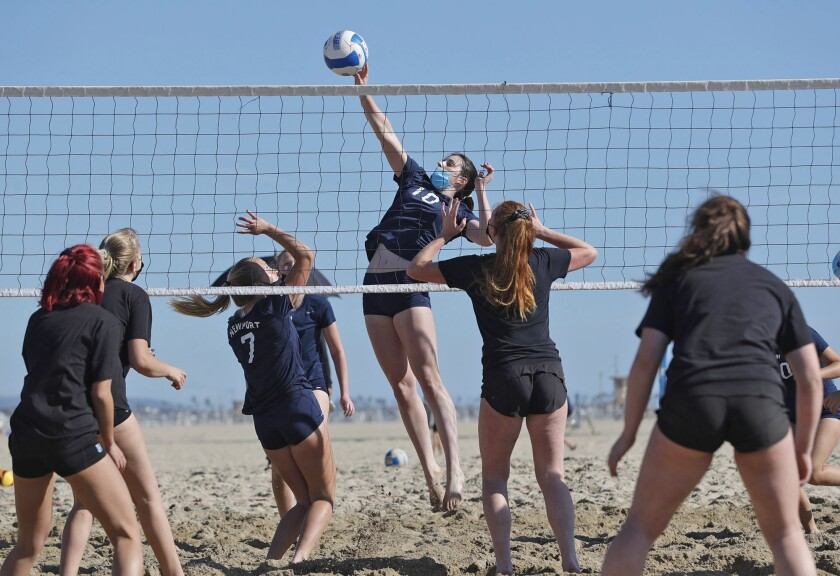 Newport Harbor's Annie O'Brien tips one over the net for a point during a beach volleyball match against Huntington Beach.