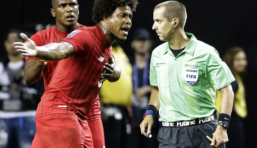 El árbitro Mark Geiger (d) es confrntado por el panameño Román Torres (c) tras favorecer a México con un penalti, en la Copa Oro.