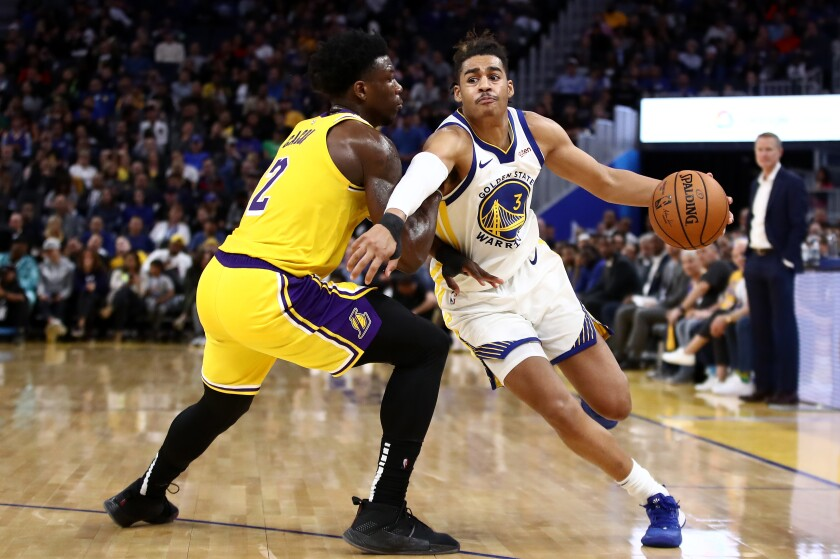 Golden State Warrior guard Jordan Poole, right, tries to drives on Lakers forward Devontae Cacok.