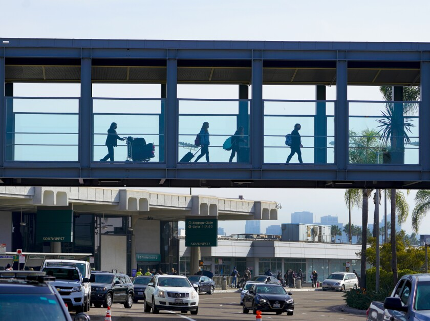 Travelers with luggage cross a bridge over traffic at San Diego International Airport
