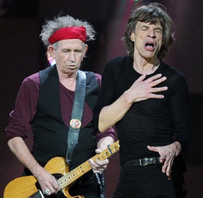 FILE - In this Dec. 12, 2012 file image released by Starpix, Keith Richards, left, and Mick Jagger of The Rolling Stones perform at 12-12-12 The Concert for Sandy Relief at Madison Square Garden in New York. The band is expected to release information on their upcoming tour on Wednesday, April 3, 2013. (AP Photo/Starpix, Dave Allocca, file)