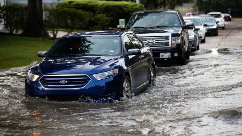 Vehicles drive on flooded streets in the aftermath of Hurricane Harvey on Wednesday, Sept. 6, 2017,