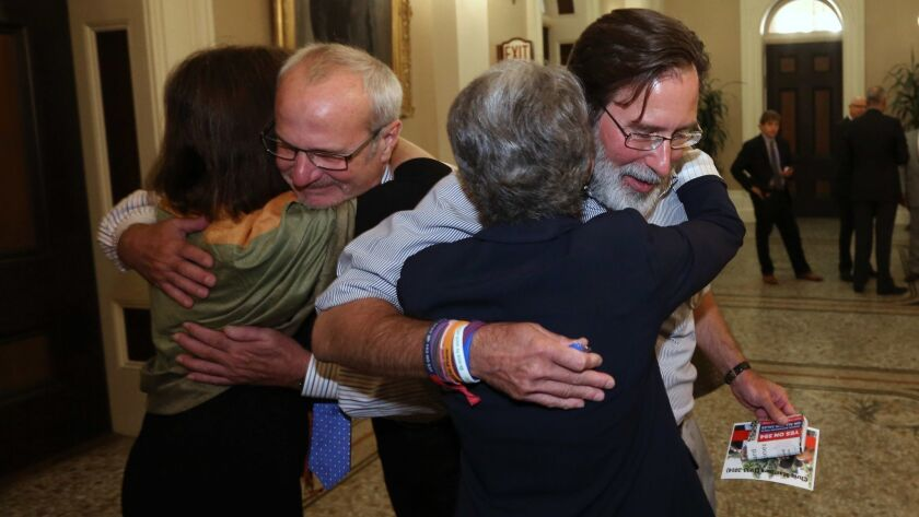 After the state Senate approved a gun removal bill in 2014, Richard Martinez, right, and Robert Weiss, who each lost a child in the Isla Vista mass shooting, celebrate with Sens. Nancy Skinner, left, and Hannah-Beth Jackson.