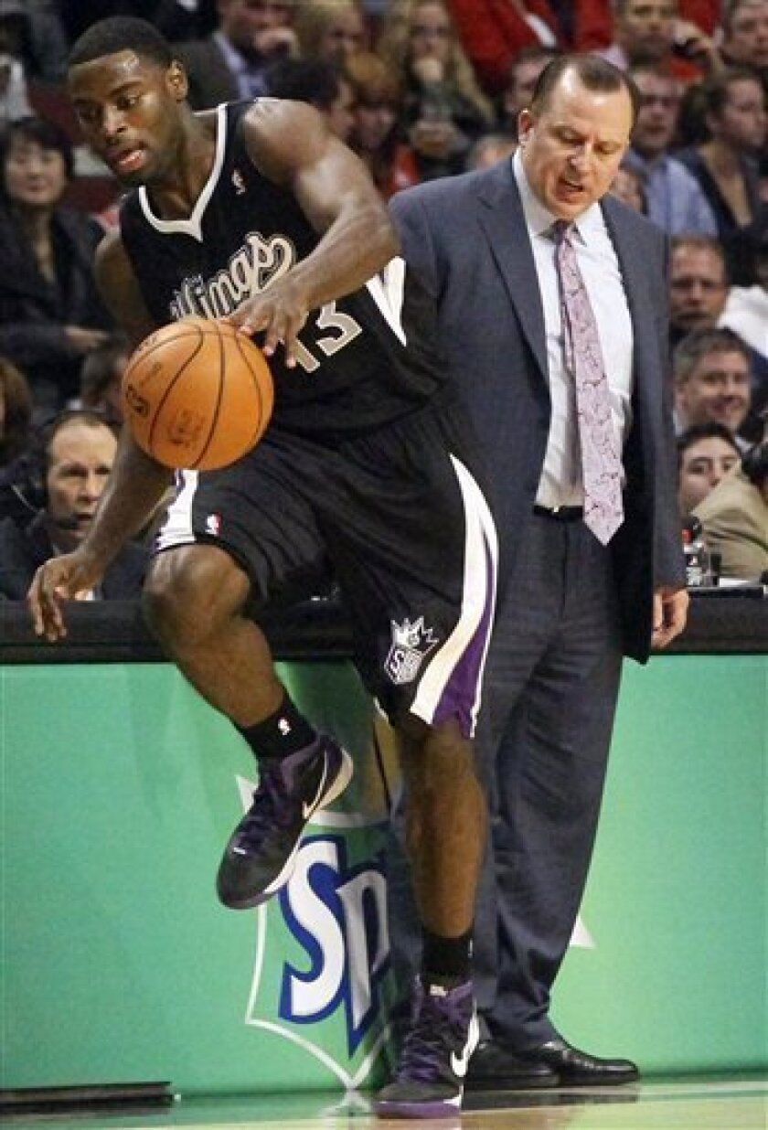 Sacramento Kings point guard Tyreke Evans (13) tries to keep the ball inbounds as Chicago Bulls head coach Tom Thibodeau watches during the first half of an NBA basketball game, Wednesday, Oct. 31, 2012, in Chicago. (AP Photo/Charles Rex Arbogast)