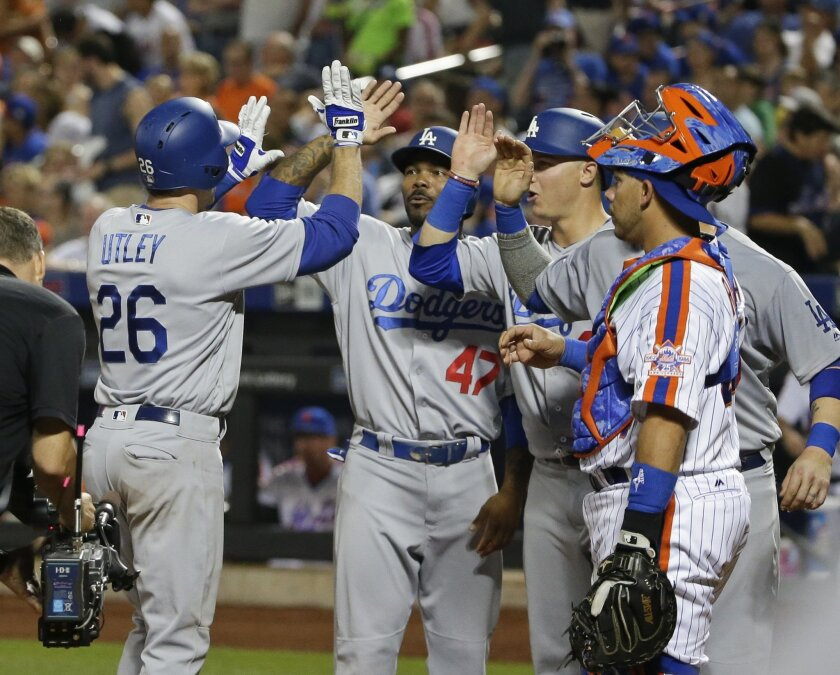 New York Mets catcher Rene Rivera (44) watches as Los Angeles Dodgers' Chase Utley (26) celebrates with teammates after hitting a grand slam home run during the seventh inning of a baseball game, Saturday, May 28, 2016, in New York. (AP Photo/Frank Franklin II)