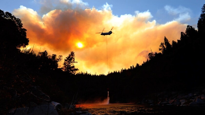 A helicopter picks up water from the Feather River to do airdrops while ground crews try to keep the Camp fire from spreading.