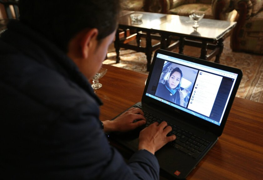In this Monday, Feb. 8, 2016, Photo, Afghan civil activist Hadi Sadiqi chats on Facebook with his wife Maleka Yawari, at his office in Kabul, Afghanistan. Young Afghans are increasingly finding love on social media, which allows them to circumvent the strict segregation of the sexes in their deeply