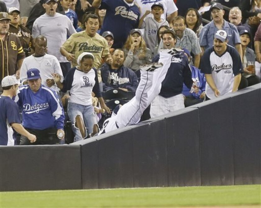 San Diego Padres left fielder Chris Denorfia falls into the stands while catching a foul fly hit by Los Angeles Dodgers' Elian Herrera during the seventh inning of a baseball game in San Diego, Thursday, June 20, 2013. (AP Photo/Lenny Ignelzi)