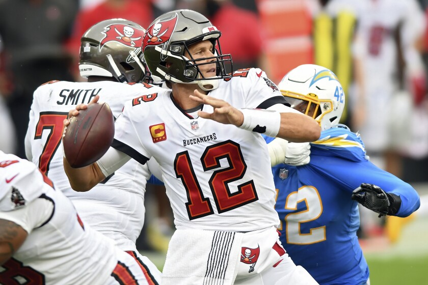 Tampa Bay Buccaneers quarterback Tom Brady (12) eludes Los Angeles Chargers linebacker Uchenna Nwosu (42) as he throws a pass during the first half of an NFL football game Sunday, Oct. 4, 2020, in Tampa, Fla. (AP Photo/Jason Behnken)