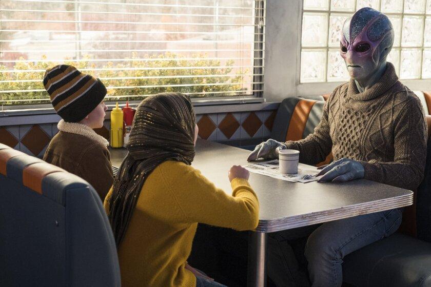 "This image released by SYFY shows Judah Prehn, from left, Gracelyn Awad Rinke and Alien Harry in the new series ""Resident Alien."" (James Dittinger/SYFY via AP)"