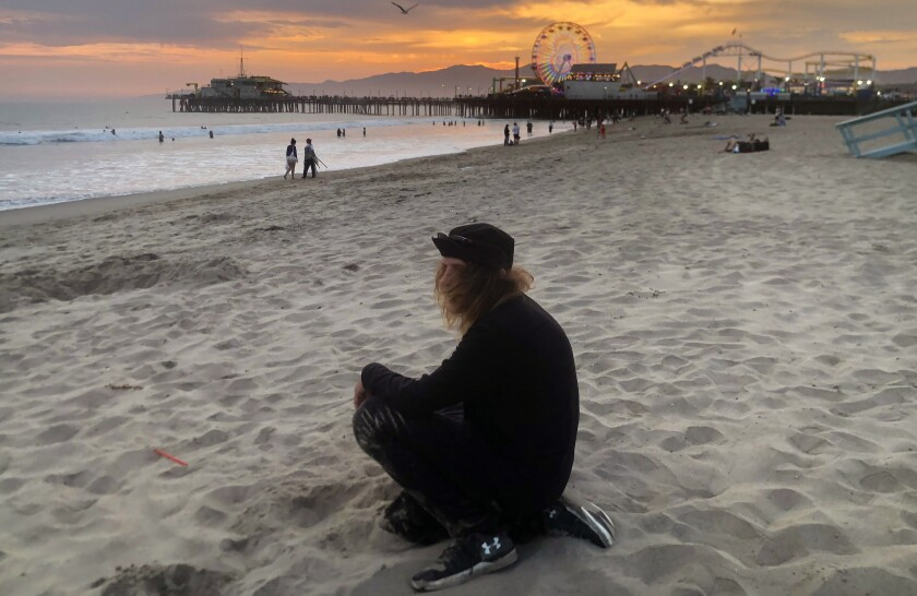 A man sits in the sand with the pier and beach in the background at sunset